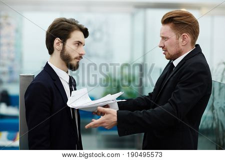 Boss critisizing one of his employees in office