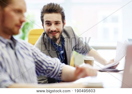 Happy young businesman talking to his colleague
