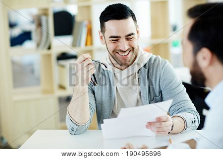 Happy businessman with papers reading them at meeting with colleague