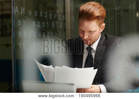 Serious economist reading financial documents in office