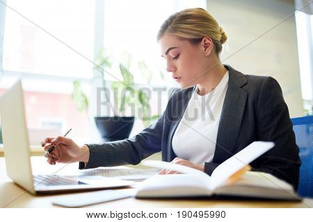 Concentrated businesswoman planning work and reading papers