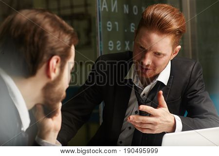 Two financial traders having discussion of data in office