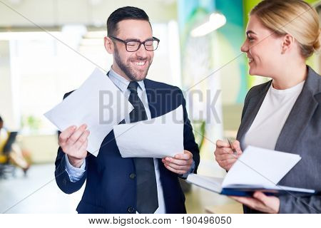 Happy employer and young manager discussing papers