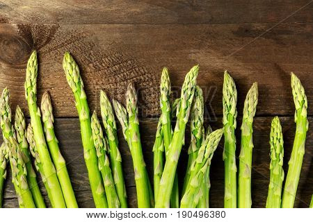 An overhead photo of fresh asparagus stalks on a rustic background with a place for text
