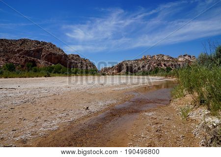 Rising global warming: wide river dried out to a tiny stream riverbed. Rising global temperature increases evaporation and reduces rainfall in arid areas reducing wide streams to tiny runlets. poster