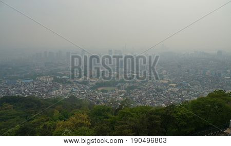 Smog over Seoul City. Skyline of downtown Seoul behind green vegetation with dense man-made smog obstructing the view. View from Namsan television tower, May 2017.