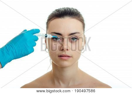 close-up portrait of a young girl without makeup at the doctor who makes her prick on her face isolated on white background
