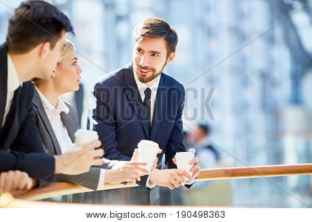 Young co-workers with coffee having talk