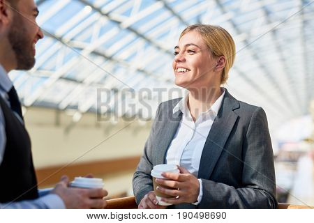 Happy woman with drink talking to her co-worker at break