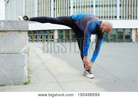 Sporty guy in activewear bending while making stretch exercise