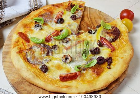 Home made pizza with smoked sausage, olives, tomates, cheese and basil on a olive wood cutting board