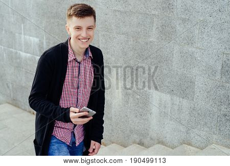 Stylish Smiling Young Man In Plaid Shirt And Jeans Walking Up Stairs And Using Smartphone Outdoors.