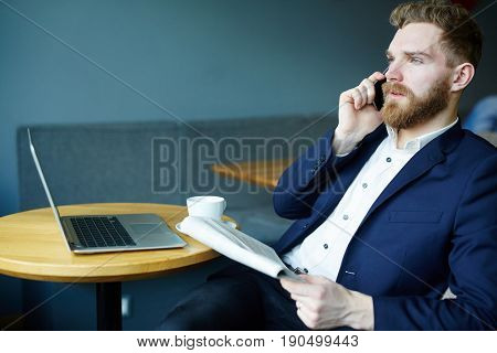 Elegant entrepreneur with newspaper talking with someone by cellphone