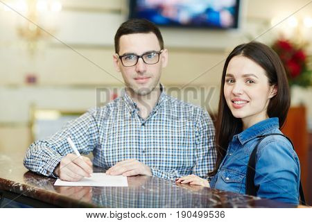 Young couple filling in registration form on arriving to hotel
