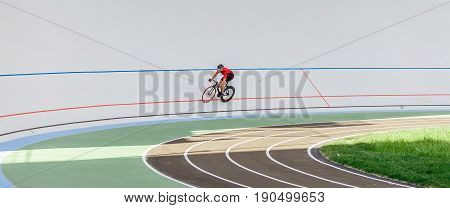 Young professional cyclist on a velodrome. Sports man in a red T-shirt and a black bicycle.