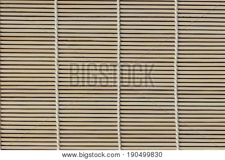 Japanese bamboo mat for rolled sushi. Close up bamboo sushi mat texture for background or wallpaper for your design. Bamboo sushi mat in macro concept for background. Wood background and texture concept.
