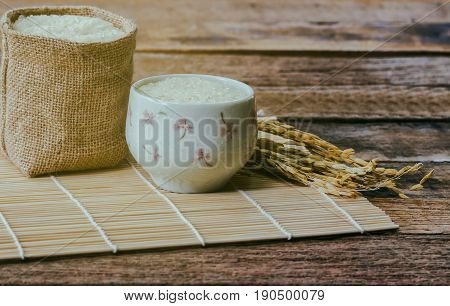 Japanese rice in gunny sack under sun light on bamboo sushi mat. Little lovely bowl filled with Japanese rice on rustic wood. Vintage warm tone style of Japanese rice of background and wallpaper. Japanese rice under sunlight concept.