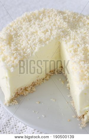 No- bake gelatin cheesecake with coconut flakes on white.