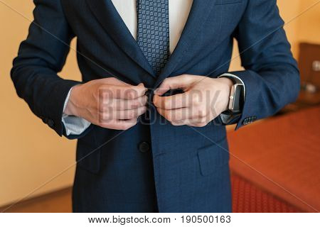 Man fastens the button on his jacket