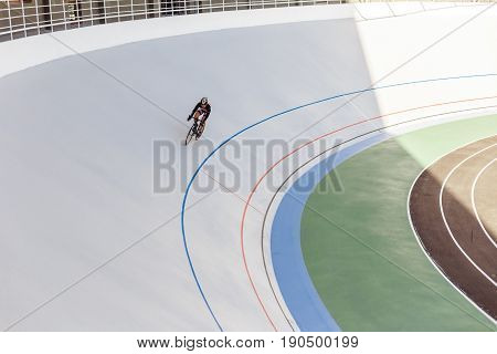 Bicyclist on cycle track outdoor. Active man racing at white velodrome.