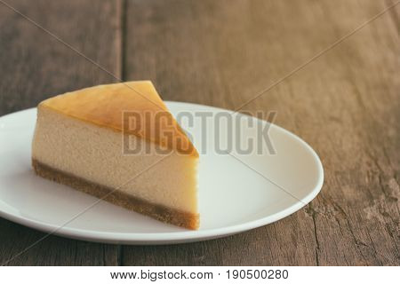Homemade New York style cheesecake on white plate. Moist and smooth baked cheesecake. Delicious plain New York cheesecake with golden brown surface on rustic wood table with copy space for background. Triangle slice of plain cheesecake.