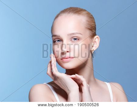 Beautiful Young Woman with Clean Fresh Skin touch own face . Facial treatment . Cosmetology beauty and spa .