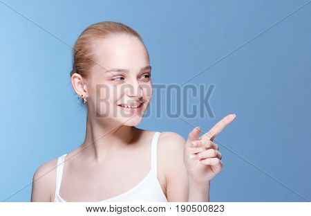 Beauty Spa Woman with perfect face skin Portrait. Girl showing empty copy space. Proposing a product. Gesture for advertisement.