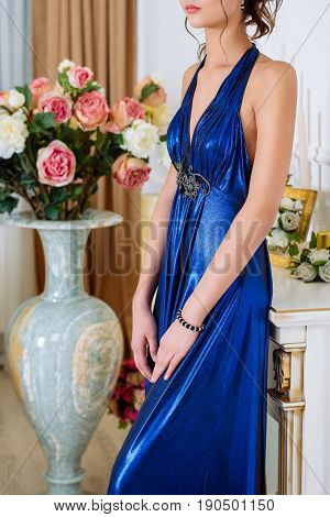 Young beautiful slim brunette girl in long blue dress with open shoulders and decollete stands near decorative fireplace and vase with flowers in the room