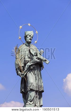 Statue of St John Nepomucene with crucifix in hand Charles Bridge Prague Czech Republic. According to the tradition St.Nomomucen was thrown out of the order of King Wenceslas IV to the Vltava in 1393.
