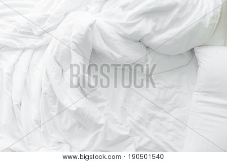 Bed sheets and pillows messed up after nights sleep , comfort and bedding concept in a hotel room, concept travel and vacation