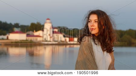 Cute young woman resting on the banks of the river at sunset.