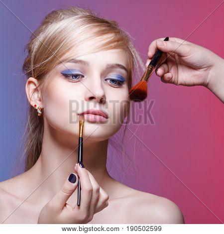 Makeup artist applies eye shadow. Beautiful woman face. Perfect makeup. Makeup detail. Beauty girl with perfect skin.