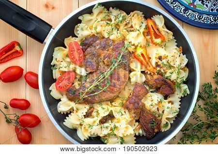 Farfalle Pasta With Roast Meat, Tomatoes Close-up On A Pan. Vertical View From Above. Close-up