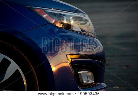 Blue Sport Sedan Under Dusk Lights At Sand Beach