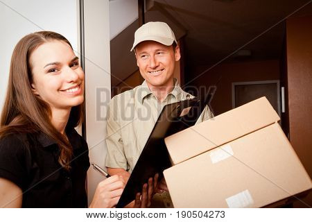 a delivery boy is hading over two packets to a young female customer. focus is on the delivery boy.