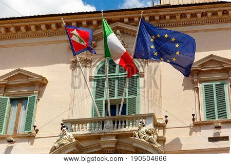 Beautiful large waving Flag of the European Union, Flag of Italy and Italian Presidential pennant on the balcony of the Quirinal Palace, Rome, Italy.