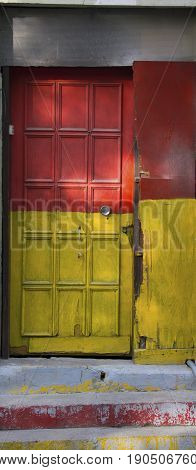 old door painted yellow and red. Neglected and worn