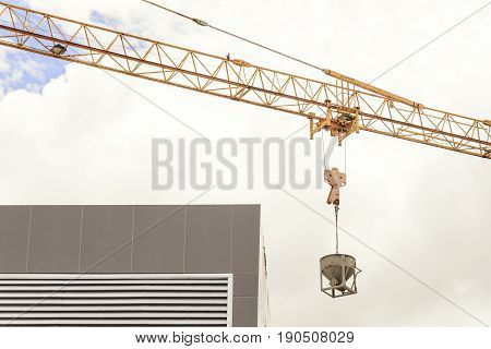 The concrete bucket attach with the hoist with the crane at construction site.Construction equipment.