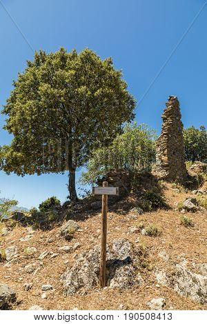 Trail sign and derelict stone walls of old buildings in the abandoned village of Case Nove near Pietralba in Balagne region of Corsica