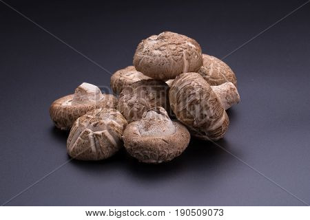 brown Shiitake mushrooms on a black table.