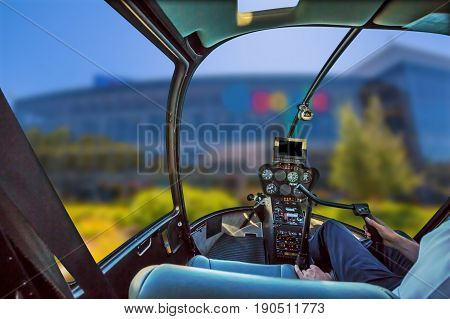 Helicopter cockpit with pilot arm and control console inside the cabin flight over Silicon Valley, California, United States. Popular Headquarter on blurred background.