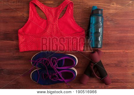 Sports and fitness equipment: dumbbells, water bottle, sports shoes and red bra on wooden background. Healthy lifestyle concept.