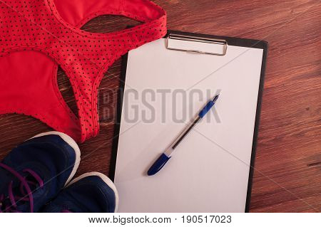 Sports and fitness equipment: sneakers, sports bra and blank clipboard with pen. Healthy lifestyle concept.