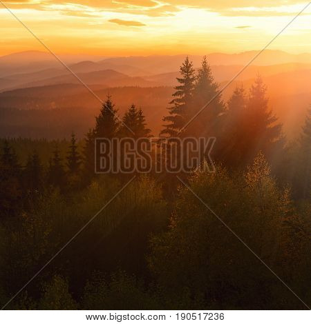 Beautiful sunset in mountains with silhouette lines and sun rays