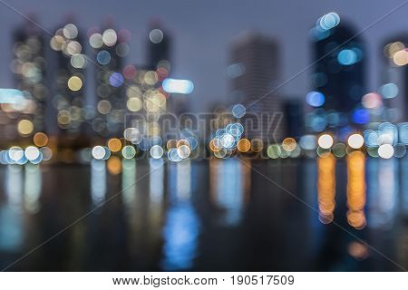 Night blurred bokeh light city building with water reflection abstract background