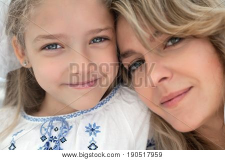 Close-up portrait of happy cheerful beautiful young mother with her little smiling daughter - outdoors.