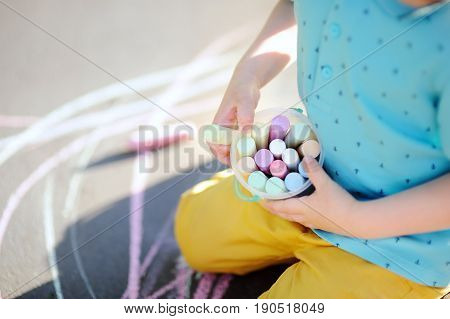Little Boy Hands Holding Box With Colorful Chalks With Drawing On Background