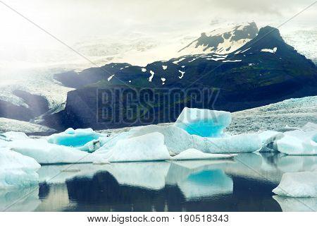 Icebergs floating in Jokulsarlon glacier lagoon with sun ray