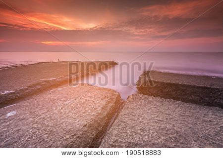 Rock on seacoast with sunrise tone natural seascape background