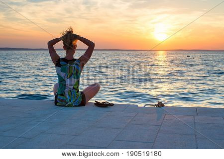 beautiful young woman sitting on a pier